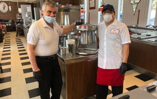 Cabots owner and employee wearing masks preparing takeout