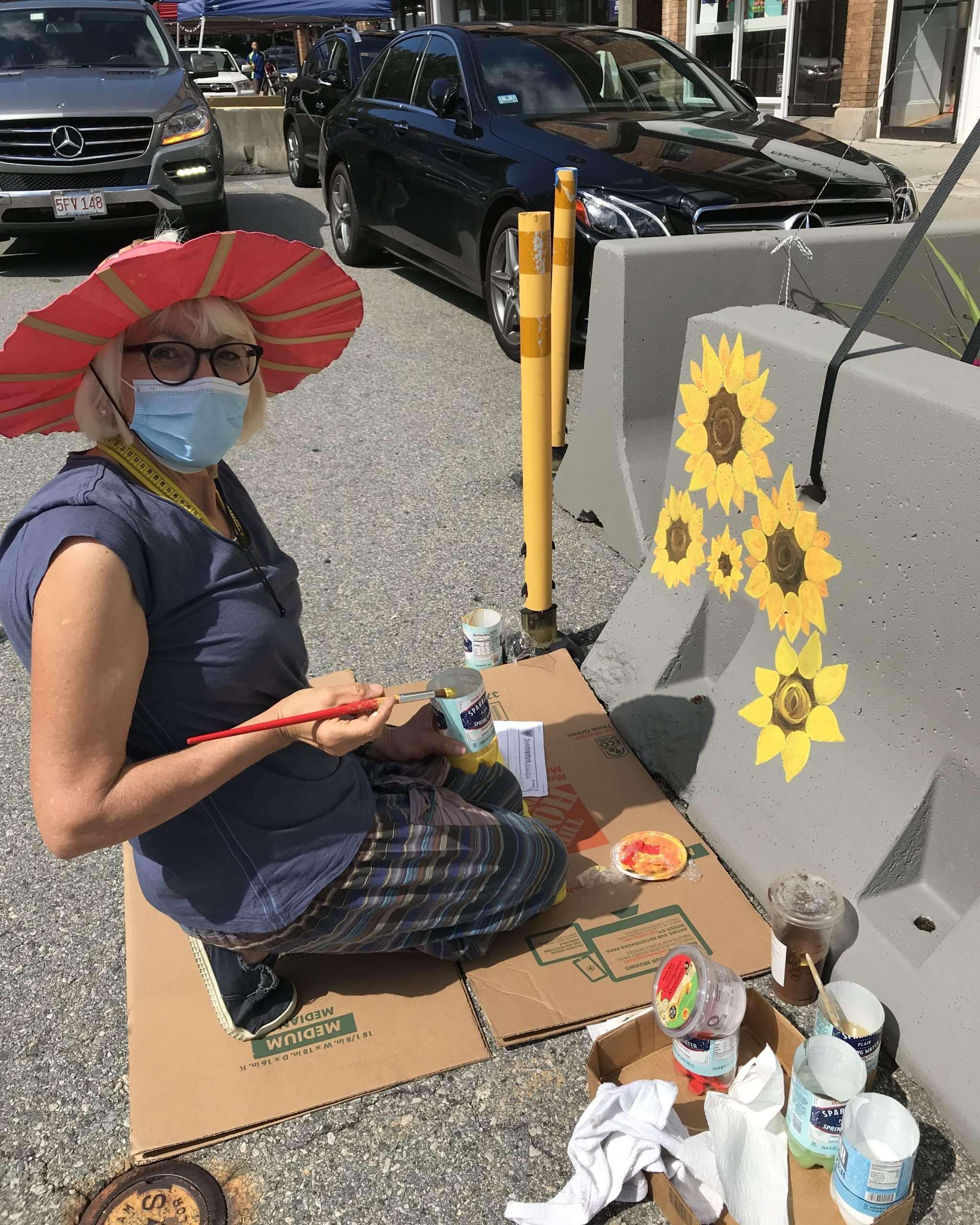 Artist paintings flowers on barriers