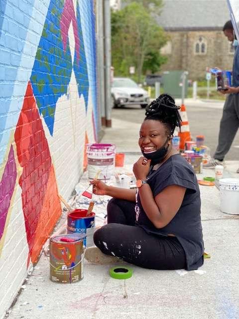 Destiny Palmer working on mural