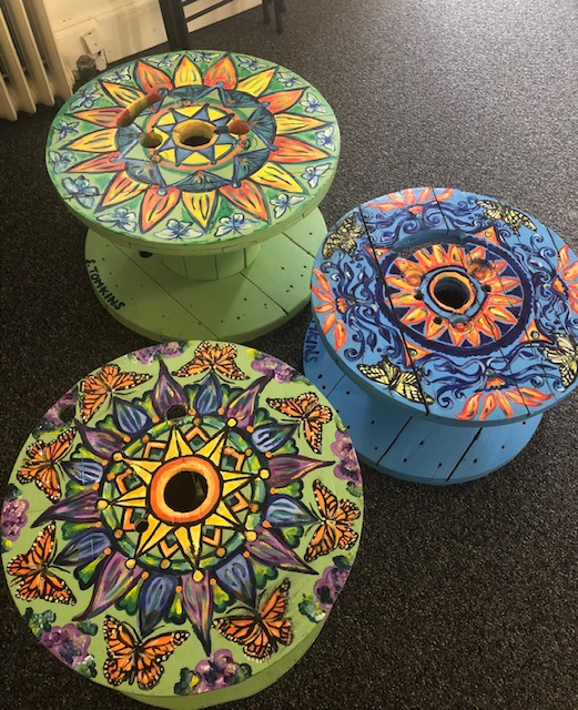 two green and one blue small tables with painted mandalas on top