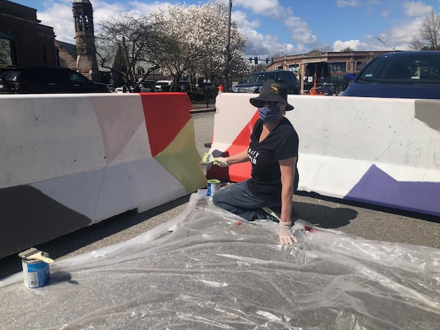 Female artist in blue hat, purple shirt and blue jeans painting a red triangle on a white barrier