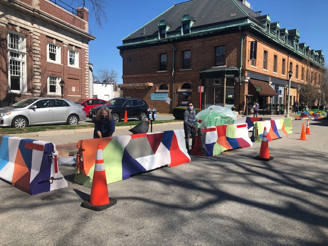 Group Painting Colorful Geometric Shapes on White Barriers