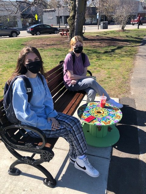two young girls with mask sitting at a bench with one of the painted side tables