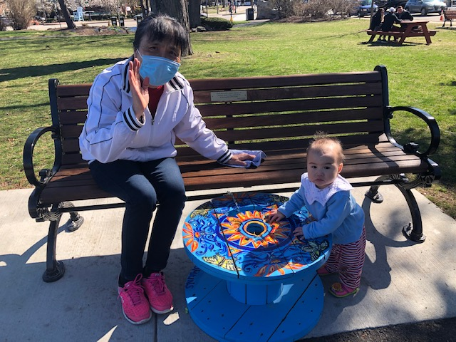 Grandma wearing mask on bench waving. Baby next to her using blue table to stand