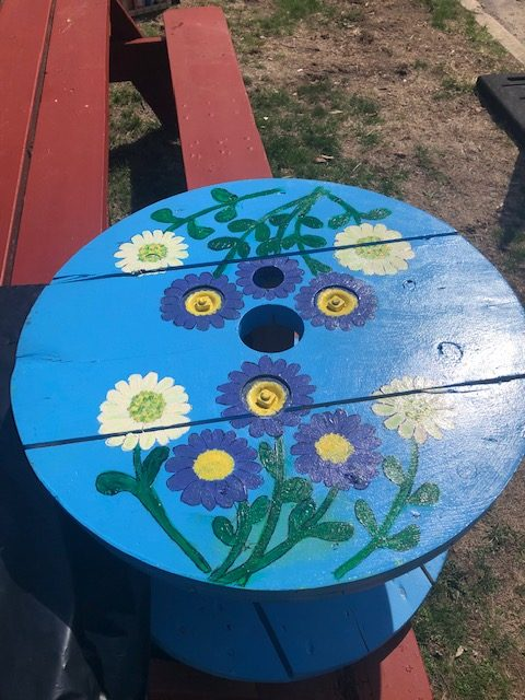 Blue table wit purple and white flowers with yellow centers and green stems