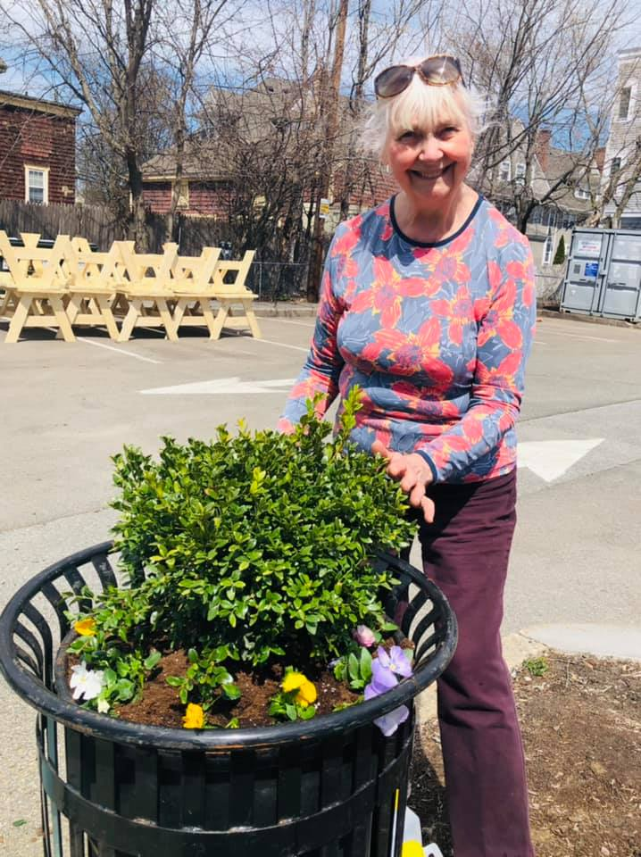 Woman in Pink clothes and white hair with sunglasses on her head smiling while planting pansies in a pot