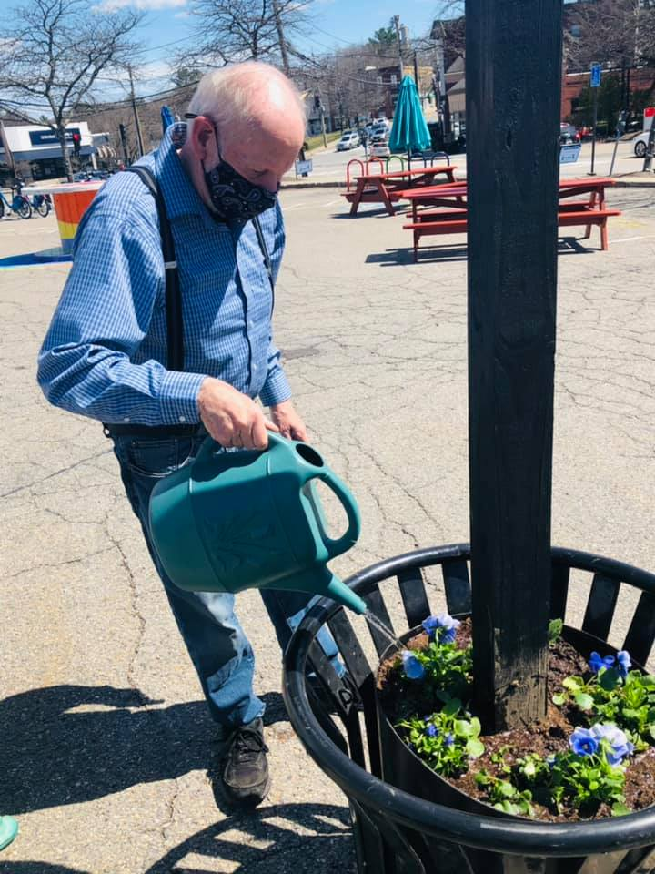 Man in Blue collared shirt in suspenders and bald head watering plants