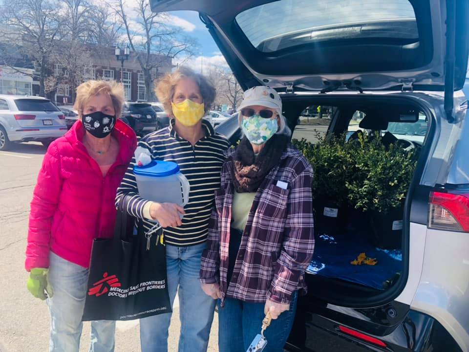 Three masked older women posing by trunk next to plants