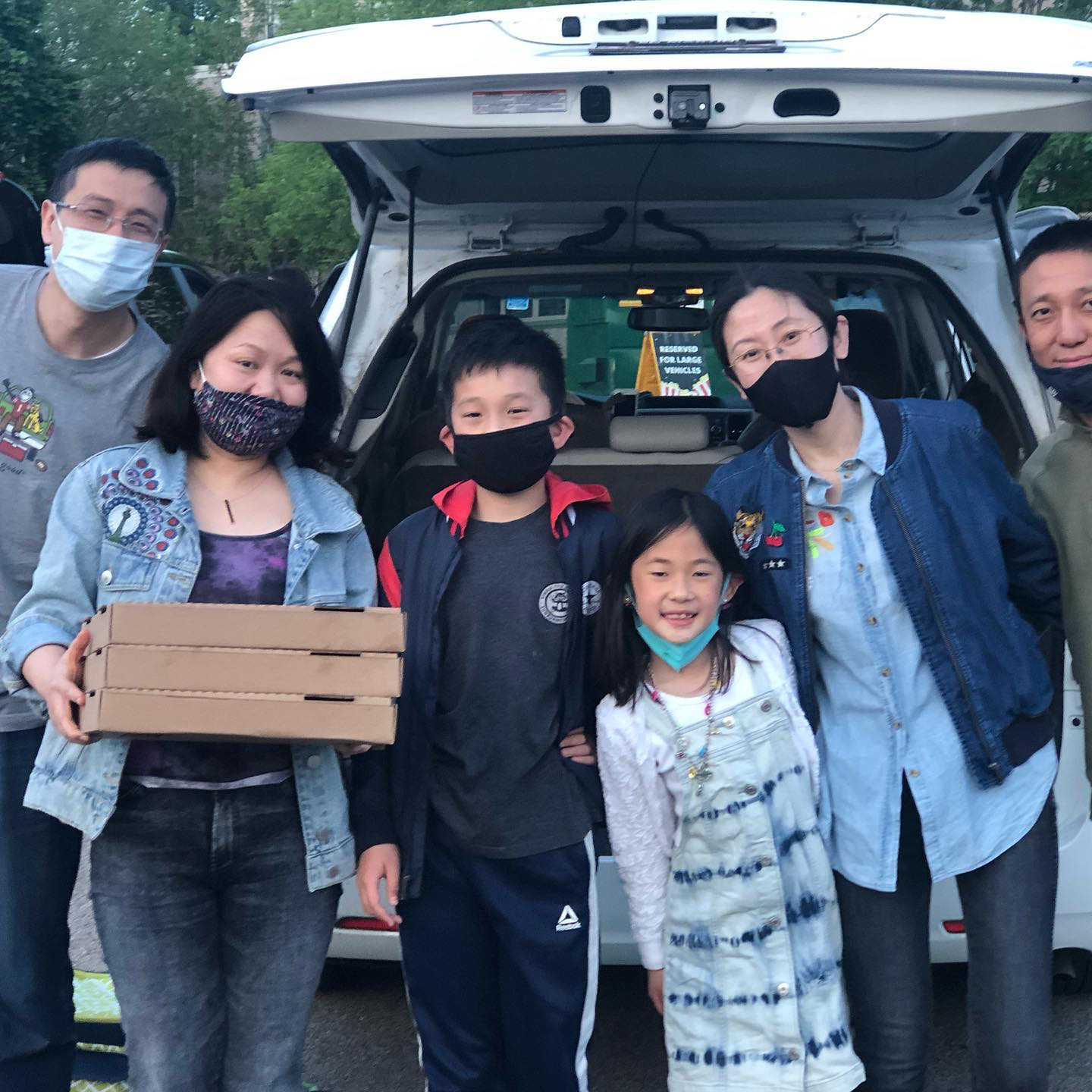 Family in front of trunk wearing masks holding pizza