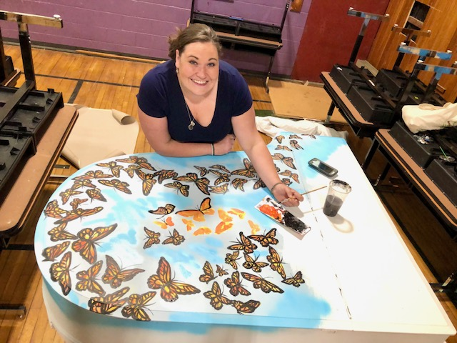 White woman with brown hair in a blue shirt painting the top of piano with butterflies