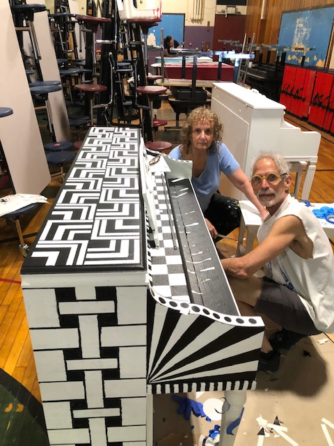 Woman with grey hair and blue shirt and man with grey hair, white tank top and orange glasses kneel down as they paint a piano in black and white geometric squares and lines