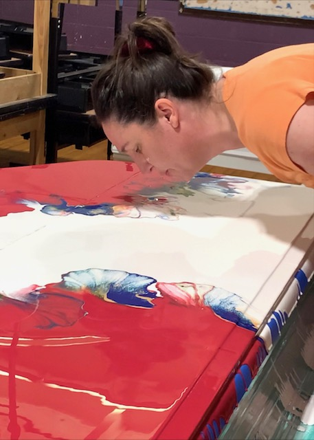 Woman with brown hair and orange shirt blowing primary color paints to make flowers on top of a piano