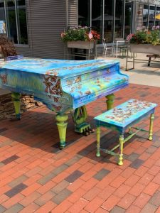 Baby Grand Piano with butterflies on it outside by a restaurant