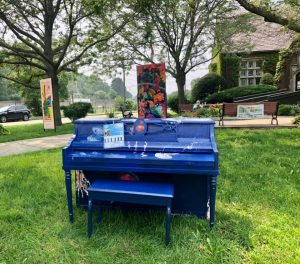 Blue Piano with Jelly Fish on grass in front of library